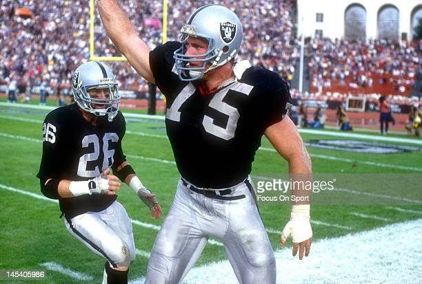 Defensive Tackle Howie Long and Van McElroy of the Los Angeles Raiders celebrates after a play against the New England Patriots during the NFL/AFC...