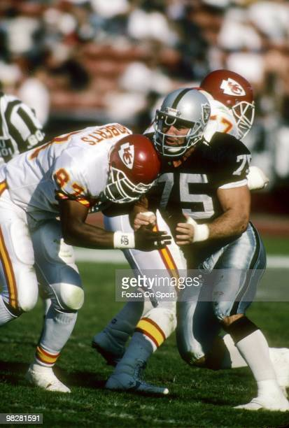 Defensive Tackle Howie Long of the Los Angeles Raiders is blocked by tightend Alfredo Roberts of the Kansas City Chiefs November 25 1990 during an...