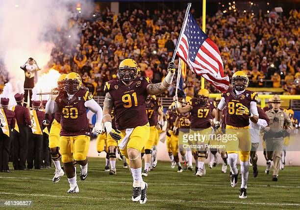 Defensive tackle Jake Sheffield of the Arizona State Sun Devils carries an American Flag as he leads teamamtes out onto the field before the Pac 12...