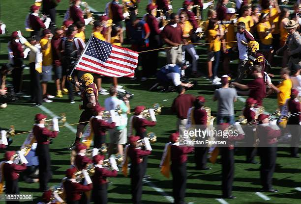 Defensive tackle Jake Sheffield of the Arizona State Sun Devils carries the American Flag out onto the field as the team is introduced before the...