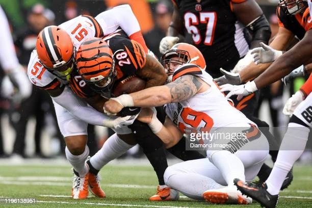 Defensive tackle Justin Zimmer and linebacker Mack Wilson of the Cleveland Browns tackle running back Joe Mixon of the Cincinnati Bengals in the...