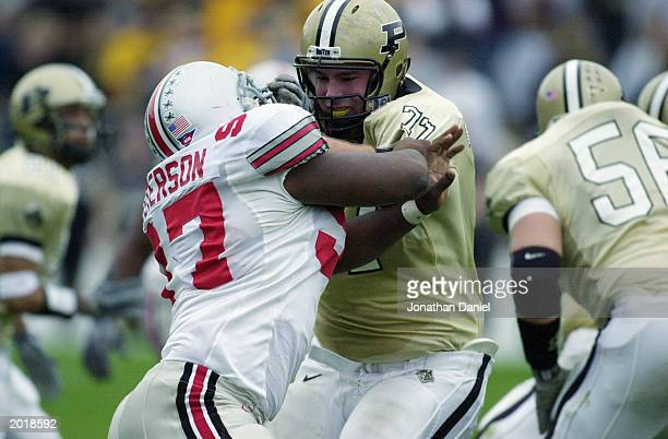 Defensive tackle Kenny Peterson of the Ohio State University Buckeyes tangles with offensive tackle Pete Lougheed of the Purdue University...