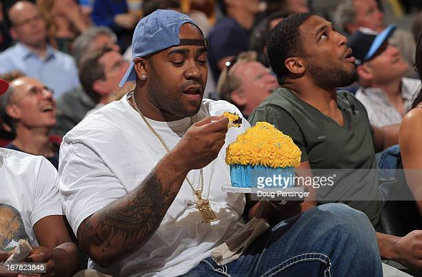 Defensive tackle Kevin Vickerson of the Denver Broncos is served a large cupcake as he sits courtside with linebacker Wesley Woodyard to see the...