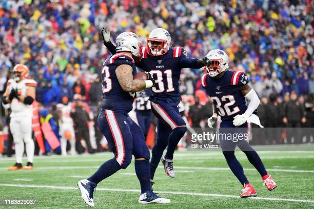 Defensive tackle Lawrence Guy of the New England Patriots celebrates an interception with teammates in the first quarter of the game against the...