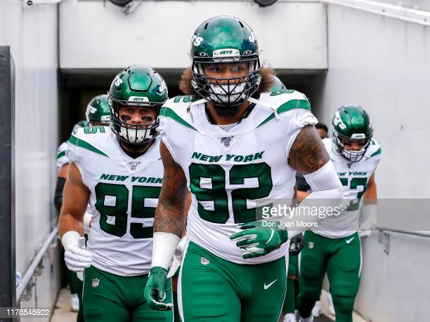 Defensive tackle Leonard Williams and tight end Trevon Wesco of the New York Jets run into the stadium before the game against the Jacksonville...