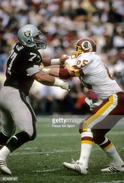 Defensive Tackle Lyle Alzado of the Los Angeles Raiders in action is blocked by tight end Don Warren of the Washington Redskins October 2 1983 during...