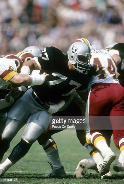 Defensive Tackle Lyle Alzado of the Los Angeles Raiders in action hits running back John Riggins off the Washington Redskins October 2 1983 during an...