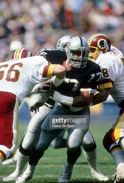 Defensive Tackle Lyle Alzado of the Los Angeles Raiders in action splits the double team of Joe Jacoby and Russ Grimm of the Washington Redskins...