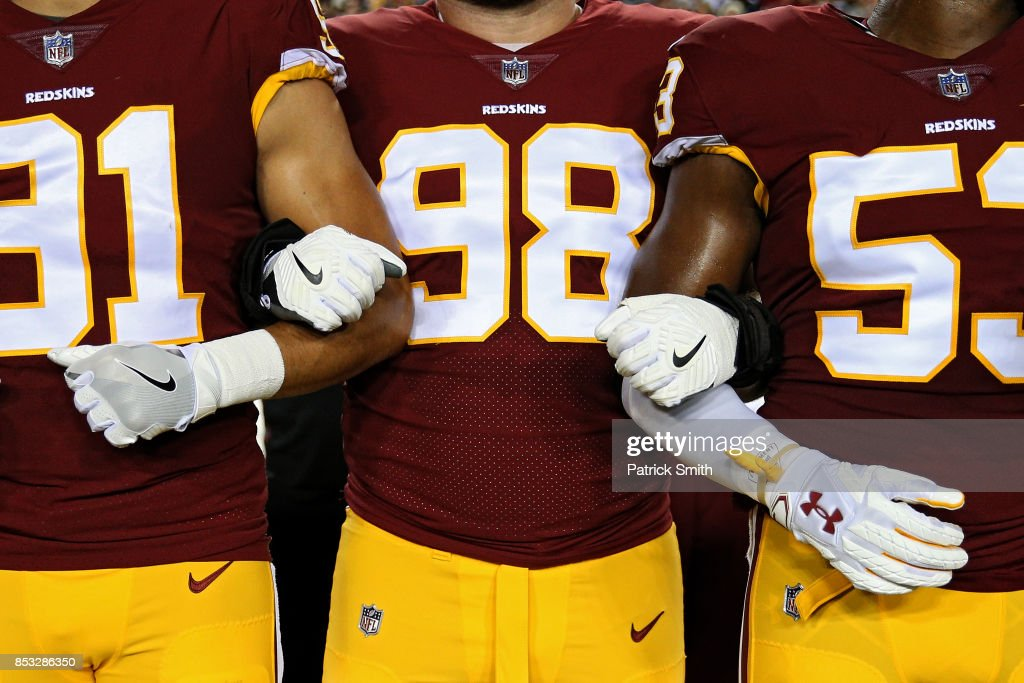 Defensive tackle Matthew Ioannidis #98 of the Washington Redskins locks arms with teammates in unison during the national anthem before playing against the Oakland Raiders at FedExField on September 24, 2017 in Landover, Maryland.