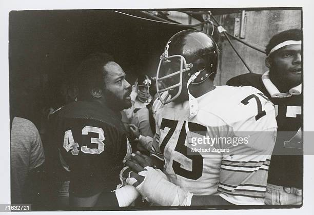 Defensive tackle 'Mean Joe' Greene of the Pittsburgh Steelers congratulates safety George Atkinson of the Oakland Raiders following the 1976 AFC...