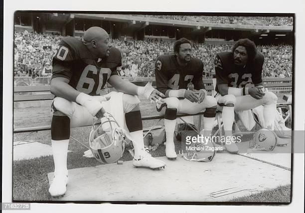 Defensive tackle Otis Sistrunk safety George Atkinson and safety Jack Tatum of the Oakland Raiders sit on the bench during the game against the San...