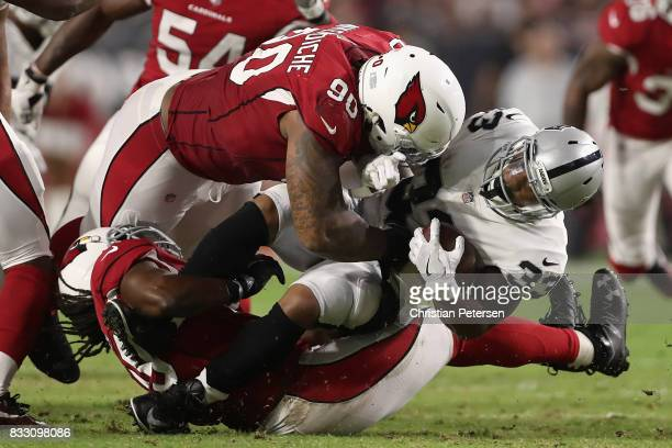 Defensive tackle Robert Nkemdiche of the Arizona Cardinals tackles running back DeAndre Washington of the Oakland Raiders for a loss during the...