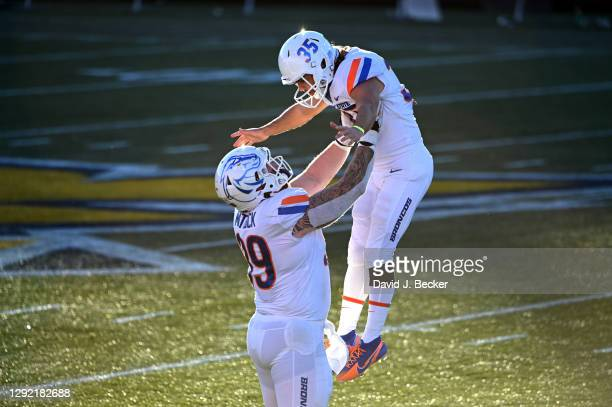 Defensive tackle Scott Matlock of the Boise State Broncos lifts kicker Jonah Dalmas after he scored a 50-yard field goal against the San Jose State...