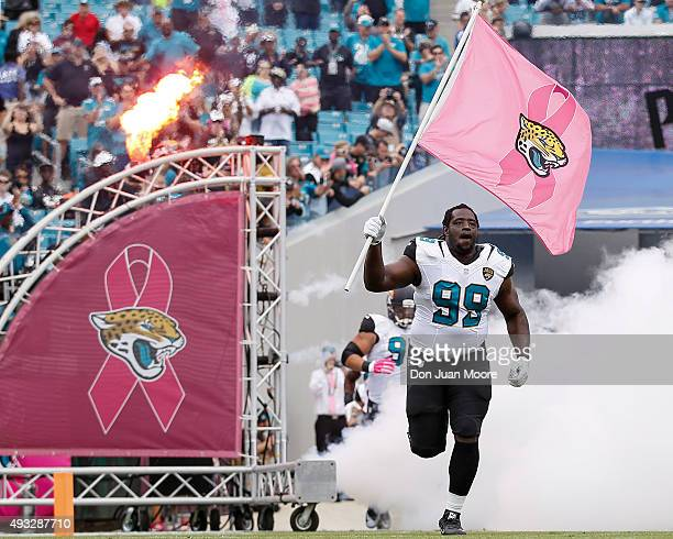 Defensive Tackle Sen'Derrick Marks of the Jacksonville Jaguars with a Jaguar Pink Flag leads the team on the field before the game against the...