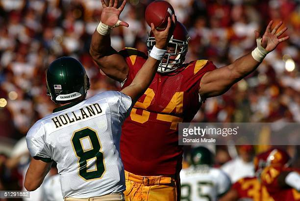 Defensive Tackle Shaun Cody of the USC Trojans places pressure on quarterback Justin Holland of the Colorado State Rams on September 11 2004 during...