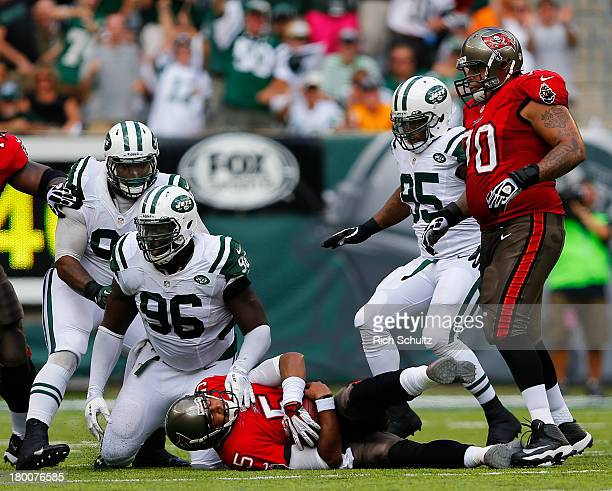 Defensive tackle Sheldon Richardson defensive end Muhammad Wilkerson and linebacker Antwan Barnes of the New York Jets sack quarterback Josh Freeman...