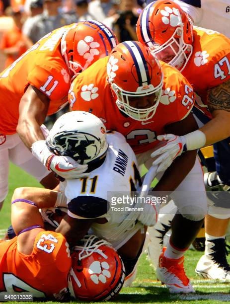 Defensive tackle Sterling Johnson of the Clemson Tigers linebacker Chad Smith linebacker James Skalski and safety Isaiah Simmons bring down running...