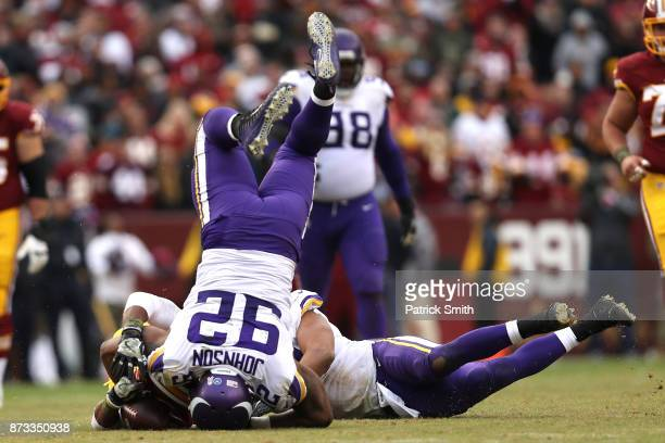 Defensive tackle Tom Johnson of the Minnesota Vikings and Eric Kendricks tackle running back Chris Thompson of the Washington Redskins during the...