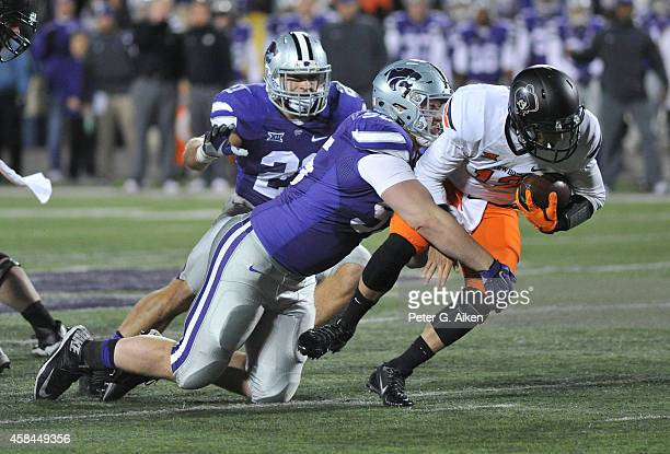 Defensive tackle Travis Britz of the Kansas State Wildcats sacks quarterback Daxx Garman of the Oklahoma State Cowboys during the first half on...