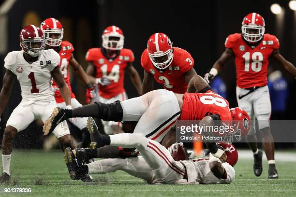 Defensive tackle Trenton Thompson of the Georgia Bulldogs tackles wide receiver Cam Sims of the Alabama Crimson Tide after a reception during the CFP...