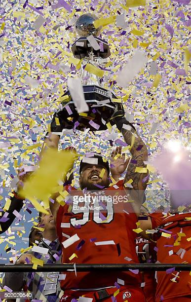 Defensive tackle Viliseni Fauonuku of the Utah Utes celebrates with the championship trophy after defeating the Brigham Young Cougars 3528 to win the...