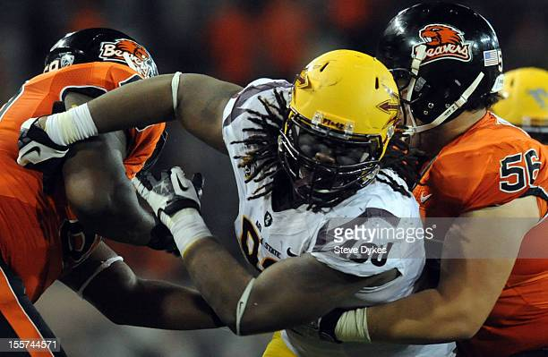 Defensive tackle Will Sutton of the Arizona State Sun Devils fights through blocks by guard Josh Andrews and offensive linesman Isaac Seumalo of the...