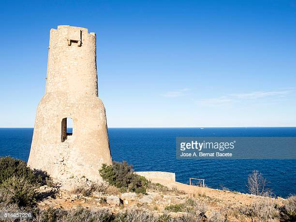 defensive tower of the 16th century on a cliff opposite to the sea - denia stock pictures, royalty-free photos & images