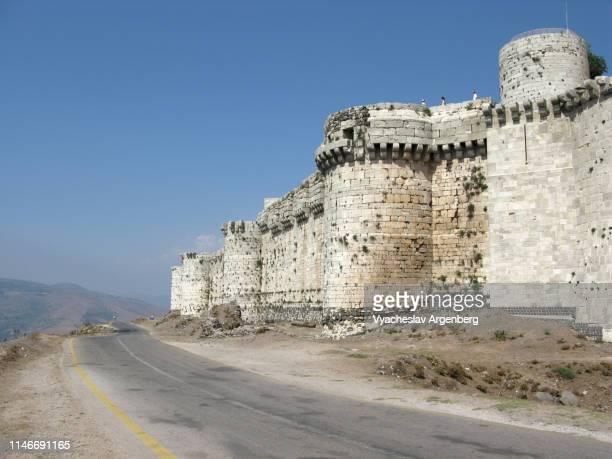 defensive walls and towers of krak des chevaliers medieval fortress, syria - argenberg - fotografias e filmes do acervo