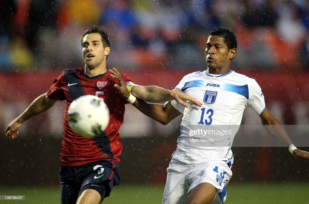 Defensman Carlos Bocanegra #5 of the USA battles with Forward Carlos Costly #13 of Honduras in the rain at Sun Life Stadium on October 8, 2011 in Miami Gardens, Florida.