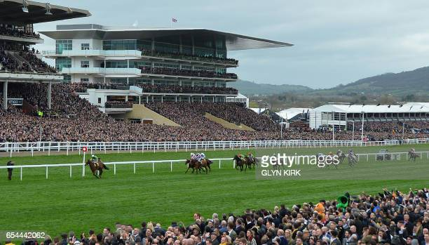 'Defi Du Seuil' ridden by English jockey Richard Johnson leads the pack to win The JCB Triumph Hurdle Race on the final day of the Cheltenham...