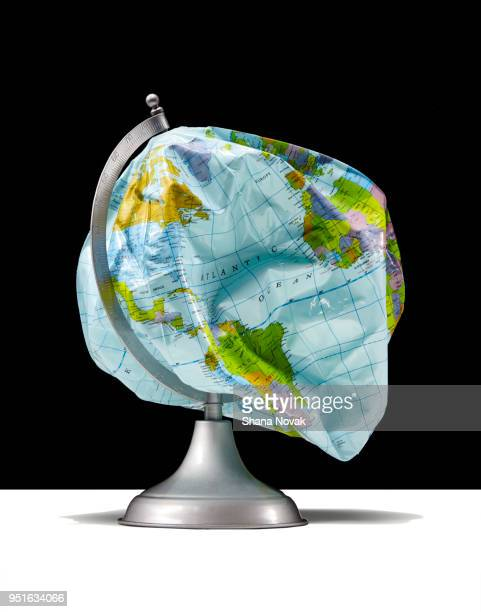 deflated globe - politics concept stock pictures, royalty-free photos & images