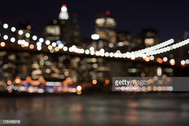 defocused abstract manhattan skyline - brooklyn bridge in front - night before stock photos and pictures