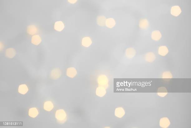 defocused blurred golden christmas lights over white background. abstract backdrop. - electric light stock pictures, royalty-free photos & images