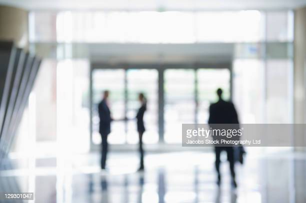defocused businesspeople in office lobby - sells arizona stock pictures, royalty-free photos & images