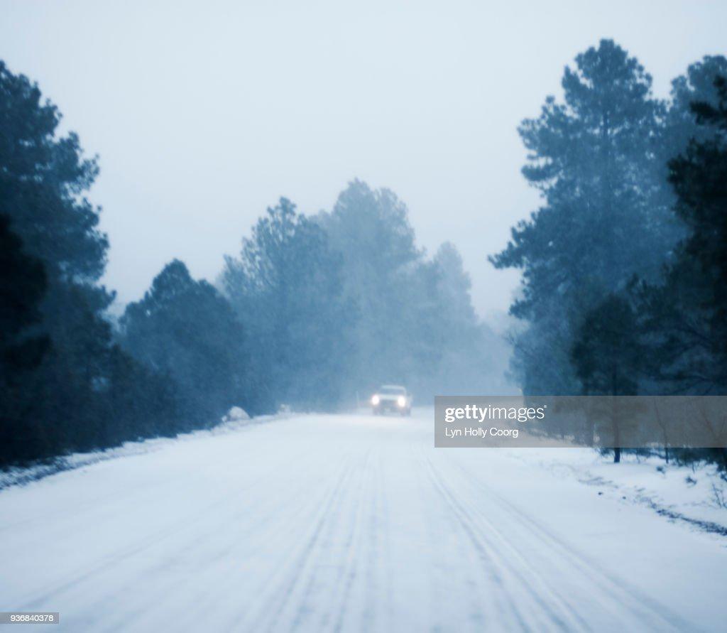 Defocused Car driving in snow along rural road : Stock Photo