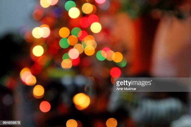 defocused christmas lights glowing - amir mukhtar stock photos and pictures