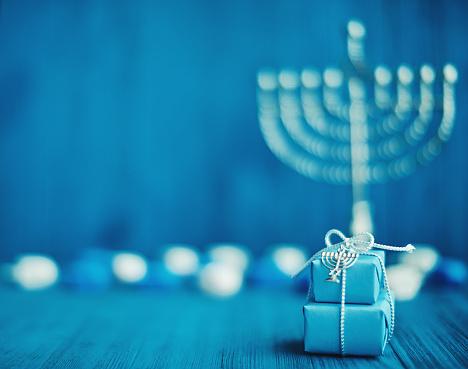 Defocused Hanukkah Background with Menorah, Gifts and Dreidel 1193220247