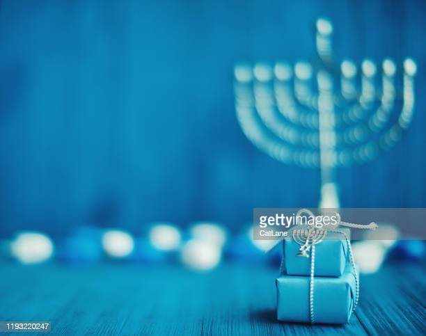 defocused hanukkah background with menorah, gifts and dreidel - hanukkah imagens e fotografias de stock