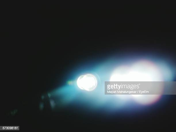defocused illuminated lights against black background - lens flare stock pictures, royalty-free photos & images