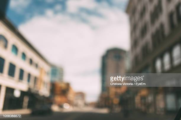 defocused image city street by buildings against sky - デフォーカス ストックフォトと画像
