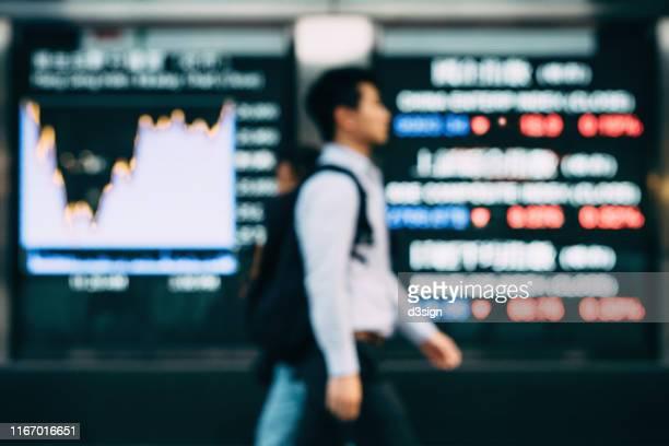 defocused image of businessman walking pass stock exchange market display screen board in downtown financial district - geld und finanzen stock-fotos und bilder