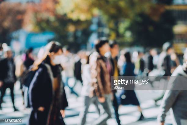 defocused image of busy commuters crossing street during office rush hours in shibuya crossroad, tokyo - 通勤 ストックフォトと画像