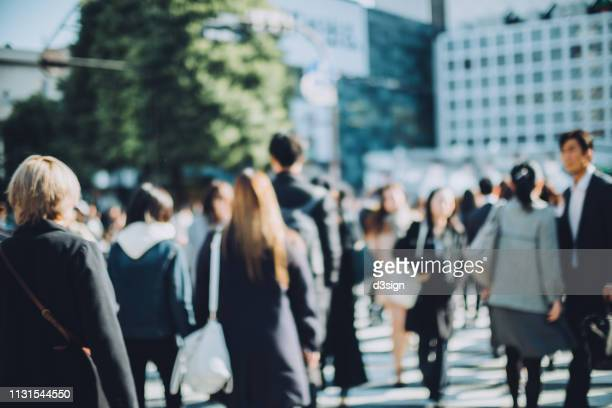 defocused image of busy commuters crossing street during rush hour in shibuya crossroad, tokyo - 商業地域 ストックフォトと画像