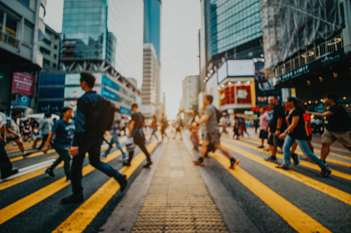 Defocused image of busy commuters crossing the street in downtown district against contemporary corporate skyscrapers - gettyimageskorea