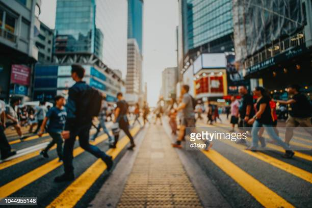defocused image of busy commuters crossing the street in downtown district against contemporary corporate skyscrapers - rush hour stock pictures, royalty-free photos & images