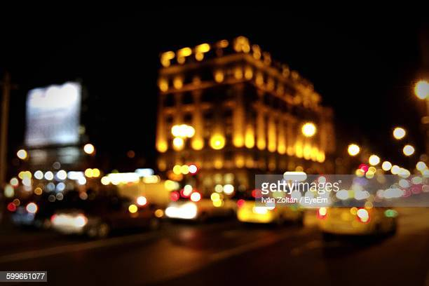 defocused image of cars on city street at night - iván zoltán stock pictures, royalty-free photos & images