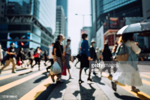 defocused image of commuters with protective face mask to protect and prevent from the spread of viruses during the coronavirus health crisis, crossing street in busy downtown district against corporate skyscrapers - stadsstraat stockfoto's en -beelden