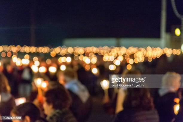 Defocused Image Of Crowd With Illuminated Candles Against Sky At Night
