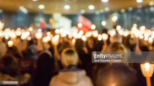 defocused image of crowd with illuminated candles in church - fatima fotografías e imágenes de stock