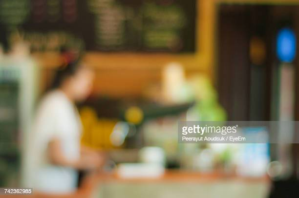 Defocused Image Of Female Worker Working At Cafe